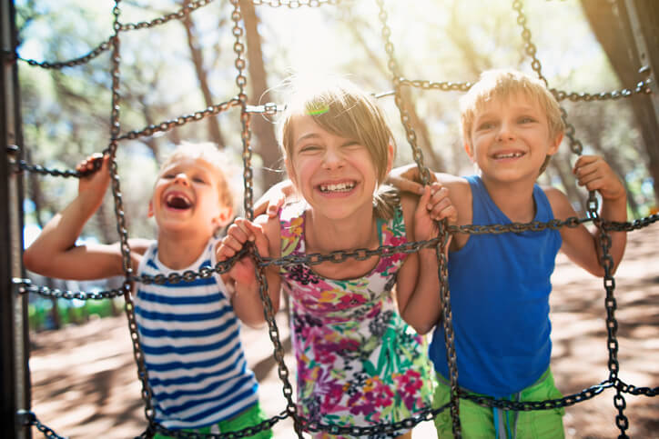 Three kids having fun at the playground. The girl aged 10 and boys aged 7 are laughing at the camera. Sunny summer day. Kids are holding climbing chains at the playground.