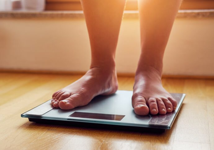 Female bare feet on weight scale at sunshine
